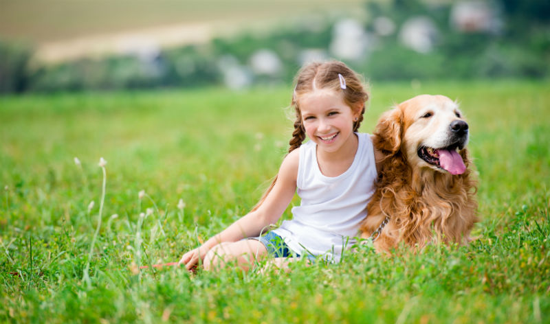 Girl and dog sitting on the grass outdoors